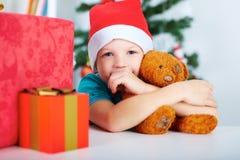 Το μικρό παιδί με τα δώρα Χριστουγέννων και Teddy αντέχουν στα χέρια, χριστουγεννιάτικο δέντρο στο υπόβαθρο Έννοια Χριστουγέννων Στοκ εικόνα με δικαίωμα ελεύθερης χρήσης