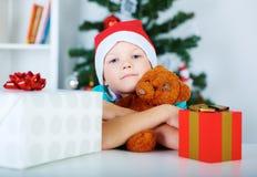 Το μικρό παιδί με τα δώρα Χριστουγέννων και Teddy αντέχουν στα χέρια, χριστουγεννιάτικο δέντρο στο υπόβαθρο Έννοια διακοπών Χριστ Στοκ φωτογραφία με δικαίωμα ελεύθερης χρήσης