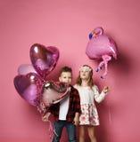 Το μικρό παιδί με τα μπαλόνια καρδιών χρώματος και το μικρό κορίτσι με το μπαλόνι φλαμίγκο είναι η γιορτή γενεθλίων ή άλλες διακο στοκ εικόνες