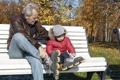 Το μικρό παιδί μιμείται τον παππού του - φορά τα σαλάχια κυλίνδρων, στοκ εικόνα