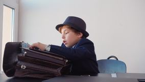 Το μικρό παιδί μοιάζει με τον επιχειρηματία, κρύβει τα χρήματα στο χαρτοφύλακα απόθεμα βίντεο