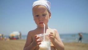 Το μικρό παιδί πίνει το κοκτέιλ μέσω του αχύρου στην παραλία απόθεμα βίντεο