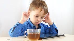 Το μικρό παιδί παίζει με την ταμπλέτα, υπάρχει ένα φλυτζάνι του τσαγιού στον πίνακα Διαδίκτυο και ασύρματες τεχνολογίες _ απόθεμα βίντεο