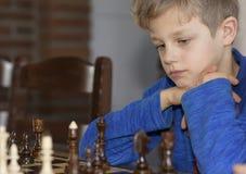 Το μικρό παιδί παίζει το σκάκι στοκ εικόνες