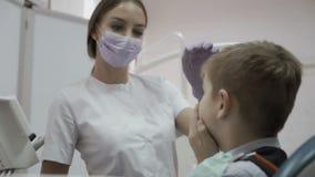 Το μικρό παιδί παραπονιέται ο οδοντίατρος για τη συνεδρίαση πονόδοντου στην καρέκλα οδοντιάτρων απόθεμα βίντεο