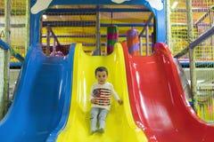 Το μικρό παιδί πηγαίνει κάτω από μια φωτογραφική διαφάνεια στην παιδική χαρά Γελά και έχει τη διασκέδαση στη γυμναστική ζουγκλών  στοκ φωτογραφία με δικαίωμα ελεύθερης χρήσης
