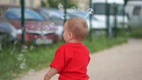 Το μικρό παιδί που κυματίζει τη ράβδο του, που κάνει το σαπούνι βράζει στην παιδική χαρά σε σε αργή κίνηση απόθεμα βίντεο