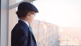 Το μικρό παιδί που μοιάζει με έναν επιχειρηματία προσέχει στο παράθυρο απόθεμα βίντεο