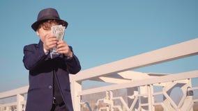Το μικρό παιδί που μοιάζει με έναν επιχειρηματία στο κοστούμι είναι υπερβαίνει τον προϋπολογισμό τα χρήματα, ρίχνει τα χρήματα στ απόθεμα βίντεο