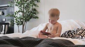Το μικρό παιδί προσέχει τα κινούμενα σχέδια στο smartphone στο κρεβάτι στο  φιλμ μικρού μήκους