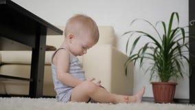 Το μικρό παιδί προσέχει τα κινούμενα σχέδια στο smartphone στο πάτωμα στο σπίτι, τρόπος ζωής απόθεμα βίντεο