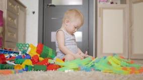 Το μικρό παιδί προσέχει τα κινούμενα σχέδια στο smartphone στο πάτωμα στο σπίτι, τρόπος ζωής φιλμ μικρού μήκους