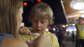 Το μικρό παιδί σε μια ασιατική αγορά νύχτας τρώει το χέρι - γίνοντα παγωτό απόθεμα βίντεο