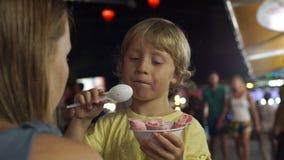 Το μικρό παιδί σε μια ασιατική αγορά νύχτας τρώει το χέρι - γίνοντα παγωτό φιλμ μικρού μήκους