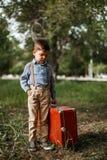 Το μικρό παιδί στα εκλεκτής ποιότητας ενδύματα με ένα καπέλο κρατά μια εκλεκτής ποιότητας βαλίτσα στοκ φωτογραφία με δικαίωμα ελεύθερης χρήσης