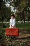 Το μικρό παιδί στα εκλεκτής ποιότητας ενδύματα με ένα καπέλο κρατά μια εκλεκτής ποιότητας βαλίτσα στοκ εικόνες