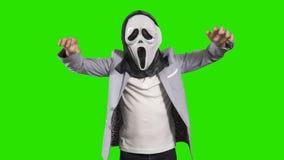 Το μικρό παιδί στη φοβερή μάσκα προσπαθεί σε τρομακτικό στο πράσινο υπόβαθρο απόθεμα βίντεο