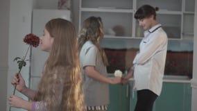 Το μικρό παιδί στις πράσινες πυτζάμες δίνει το λουλούδι στην αδελφή του στο υπόβαθρο του παλαιότερου κοριτσιού δίνει το λουλούδι  απόθεμα βίντεο