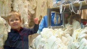Το μικρό παιδί στο εμπορικό κέντρο ζητά να αγοράσει ένα πράγμα Οι γονείς με το γιο στέκονται σε ένα επίδειξη-παράθυρο του καταστή φιλμ μικρού μήκους