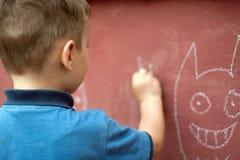 Το μικρό παιδί σύρει με την κιμωλία στοκ φωτογραφίες με δικαίωμα ελεύθερης χρήσης