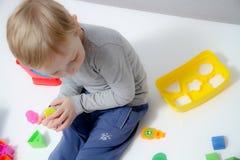 Το μικρό παιδί τρία χρονών κάθεται στον πίνακα και παίζει Στοκ Φωτογραφίες