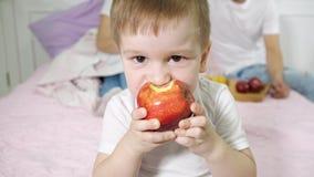 Το μικρό παιδί τρώει το μήλο στην κρεβατοκάμαρα του γονέα Οι γονείς του που κάθονται στο κρεβάτι στο υπόβαθρο απόθεμα βίντεο