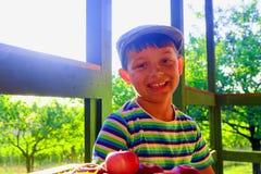 Το μικρό παιδί φορά την επίπεδη ΚΑΠ Μήλα και σταφύλια σε έναν πίνακα Το χαμογελώντας μικρό παιδί κάθεται σε έναν πίνακα σε μια βε στοκ εικόνα με δικαίωμα ελεύθερης χρήσης