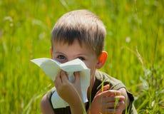 Το μικρό παιδί φυσά τη μύτη του στοκ εικόνα
