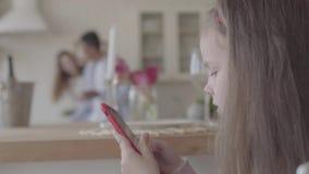 Το μικρό παιχνίδι κοριτσιών με το κινητό τηλέφωνο και στο υπόβαθρο είναι η μητέρα και ο πατέρας της στη μεγάλη κουζίνα φιλμ μικρού μήκους