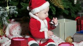 Το μικρό παιδί Άγιου Βασίλη, μωρό στο κοστούμι Santa, που παίζει με τα γυαλιά, παιδί κάθεται στα κοστούμια καρναβαλιού, Χριστούγε απόθεμα βίντεο