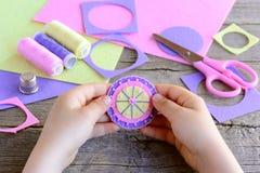 Το μικρό παιδί έκανε ένα απλό και ζωηρόχρωμο λουλούδι από τους αισθητούς κύκλους και τις χάντρες Το παιδί κρατά ένα φωτεινό αισθη Στοκ Εικόνες