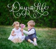 Το μικρό παιδί δίνει σε ένα κορίτσι μια ανθοδέσμη των λουλουδιών και της ημέρας κειμένων στη ζωή Η καλλιγραφία που γράφει το εκλε Στοκ φωτογραφία με δικαίωμα ελεύθερης χρήσης