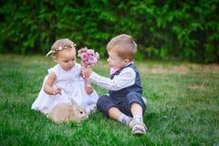 Το μικρό παιδί δίνει σε ένα κορίτσι μια ανθοδέσμη των λουλουδιών Στοκ Φωτογραφία