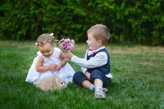 Το μικρό παιδί δίνει σε ένα κορίτσι μια ανθοδέσμη των λουλουδιών Στοκ φωτογραφίες με δικαίωμα ελεύθερης χρήσης