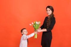 Το μικρό παιδί δίνει σε ένα κορίτσι μια ανθοδέσμη των λουλουδιών Στοκ Φωτογραφίες