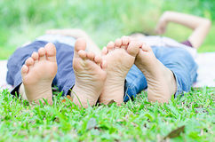 Το μικρό παιδί βάζει στη χλόη παρουσιάζει πόδια Στοκ Εικόνες