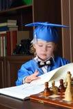 Το μικρό παιδί βγάζει φύλλα μέσω ενός βιβλίου Στοκ Φωτογραφίες