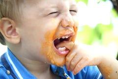 Το μικρό παιδί γελά και τρώει Στοκ Εικόνα