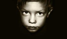 Το μικρό παιδί εξετάζει το φακό Στοκ Φωτογραφία