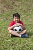 Το μικρό παιδί θέτει τη σφαίρα ποδοσφαίρου στον πράσινο τομέα χλόης Στοκ φωτογραφία με δικαίωμα ελεύθερης χρήσης