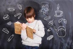 Το μικρό παιδί διαβάζει το βιβλίο Στοκ Φωτογραφίες