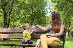 Το μικρό παιδί κάθεται με τη μητέρα του σε έναν πάγκο και πίνει το νερό Στοκ Εικόνες