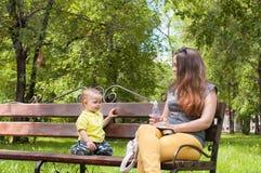 Το μικρό παιδί κάθεται με τη μητέρα του σε έναν πάγκο και πίνει το νερό Στοκ φωτογραφία με δικαίωμα ελεύθερης χρήσης