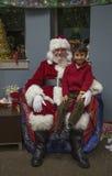 Το μικρό παιδί κάθεται στην περιτύλιξη Santa στο γεύμα Χριστουγέννων για τους αμερικανικούς στρατιώτες στο πληγωμένο κέντρο πολεμ Στοκ Εικόνα
