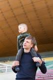 Το μικρό παιδί κάθεται στους ώμους του πατέρα Στοκ φωτογραφία με δικαίωμα ελεύθερης χρήσης