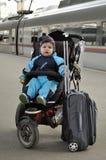 Το μικρό παιδί κάθεται στο καροτσάκι με τις αποσκευές στο σιδηροδρομικό σταθμό Στοκ Εικόνα