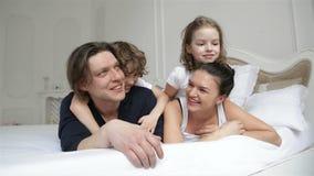 Το μικρό παιδί και το κορίτσι με δύο ενηλίκους χαλαρώνουν μαζί στο άσπρο κρεβάτι γονέων Πορτρέτο των νέων εξόδων ζεύγους απόθεμα βίντεο