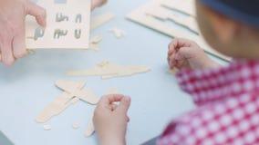 Το μικρό παιδί και το mom του στηρίζονται ένα ξύλινο αεροπλάνο στον πίνακα απόθεμα βίντεο