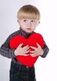 Το μικρό παιδί κρατά την καρδιά απομονωμένη στο λευκό Στοκ Φωτογραφία