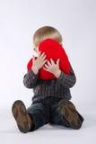 Το μικρό παιδί κρατά την καρδιά απομονωμένη στο λευκό Στοκ Εικόνες